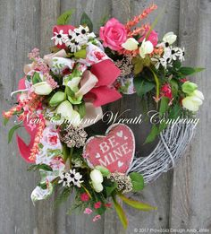Cottage Valentine Heart Wreath. Romantic hues of blush pink, soft salmon, spring green and winter white are featured in lush blossoms, wildflowers, meadow grass and greenery, gathering graciously upon