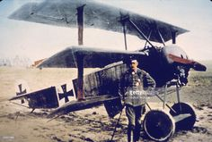 German flying ace Heinrich Gontermann (1896 - 1917) stands near his Fokker DR-1 tri-plane on an airfield, Germany, 1910s. Gontermann, who had 39 victories as a fighter pilot, was killed in this aircraft when it broke up in the air and the DR-1 was removed from service. The DR-1 was designed by aircraft manufacturer Anthony Fokker, known as the 'Flying Dutchman,' and was the plane used by the famous flying ace the Red Baron.
