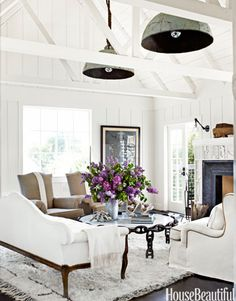 """In a Marin County, California, beach house designed by Erin Martin and homeowner Kim Dempster, thirty-inch buoy lights, from Erin Martin Design, hang from ropes. """"The ceiling is high and narrow, and the lights bring it down and create a kind of canopy,"""" Martin says. """"It's like putting a hat on the space."""" A pair of antique French chairs are upholstered in natural linen."""