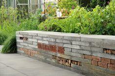 Keermuurtje in de Inclusieve Tuin. Het muurtje is door zijn hoogte van 45cm ook geschikt als zitrand. Het muurtje is opgebouwd van betontegels, afgewisseld met bakstenen, isolatiestenen en takken en stammetjes. Zo is het muurtje ook geschikt voor allerlei insecten: onmisbaar in een gezonde tuin.   Ontwerp: Studio Toop. In opdracht van: Vara's Vroege Vogels en Groei