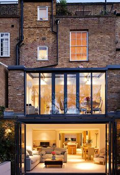 Two story house extension at the back with floor to ceiling glass walls.