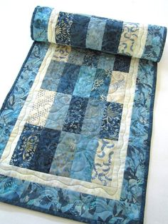 """This table runner is made using a variety of blue fabrics. This runner will be a beautiful setting for your table. This runner would also be a wonderful gift to give someone. This table runner is 16"""""""