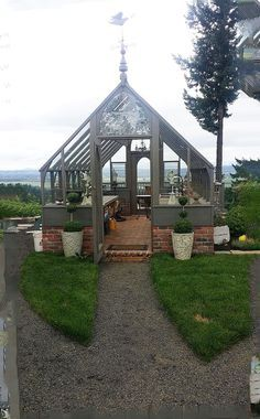 Tudor Model Greenhouse from Sturdi-Built Greenhouse Mfg. with deck, dining area, cut glass window, weather vane. Greenhouse done to PERFECTION