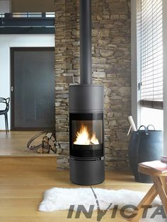 The Alcor wood burning fireplace is sleek, elegant and fuel efficient. With panoramic curved glass and strong cast iron body, it fits easily into compact spaces Decor, Wood, Hearth, Fireplace Accessories, Fireplace Design, Stove, Modern Fireplace, Home Decor Catalogs, Wood Burning Stove