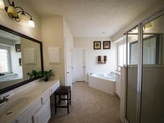 The master bath has his and her sink areas, framed mirrors, and a large separate shower.