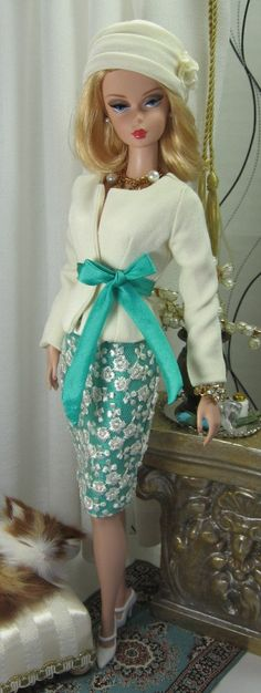 This two piece ensemble starts with a collarless jacket in cream suiting, fully lined, with long sleeves, and one button or snap front closure. A sash of brilliant emerald silk tissue ties at the waistline. The pencil skirt is emerald silk tissue overlayed with a piece of luxurious cream lace and lined in emerald china silk. Button over snaps closes the back. The bias cut hat is cream suiting, fully lined, and finished with cream china silk florals with brilliant emerald bead ...