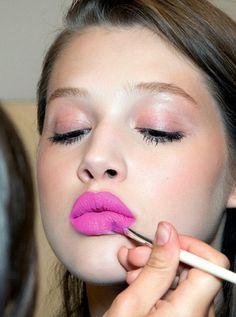 A pop of color on lips with soft eyes and cheeks is pretty for a spring wedding.