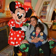 Minnie posing with a couple guest at her home in Disneyland.