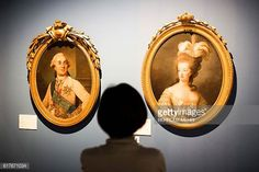 A woman looks at portraits of King of France Louis XVI