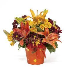Cubito con 3 tallos de lilium y 5 tallos de margaritas en tonos rojizos y amarillos y verdes decorativos.