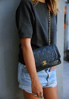 Style with an ease: Vintage denim shorts, a black tee and a quilted bag.