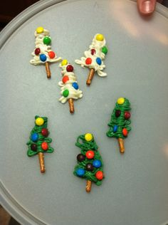 Pretzel stick Christmas trees with mini M&Ms! I used colored chocolate (Wilton's), melted in a ziplock bag for 1-2 minutes at 30 sec intervals. Cut a tiny but off of one corner and pipe in the shape of a tree, then let the kids decorate. Fun and super easy! Makes a lot! White and green chocolate candy melts Mini pretzel sticks Mini M&Ms Ziplock bag Wax paper :)