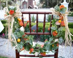 Roses and citrus fruit add color and texture to the backs of these wedding chairs