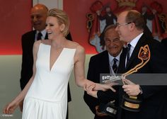 Prince Albert II of Monaco (R) and his wife Princess Charlene share a laugh on the podium during the Monaco Formula One Grand Prix at the Monaco street circuit in Monte-Carlo on May 24, 2015. AFP PHOTO / BORIS HORVAT