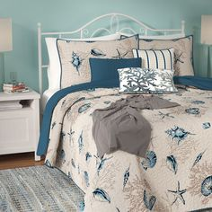 Bring a bit of coastal charm and patterned appeal to your master suite or guest room with this essential polyester microfiber coverlet set, featuring sea fans, starfish, and shells in neutral and blue colors. Set it on a cream-finished metal bed in the master suite or guest room to lean into the neutral, cool palette, then add in matching navy blue pillow shams and folded teal blankets onto the bedspread to tie the whole ensemble together. Add in cozy cotton sheets and down-fill pillows to…