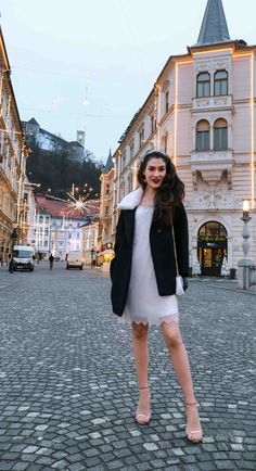 Fashion Blogger Veronika Lipar of Brunette from Wall Street dressed in white sequinned dress, short loose black and white coat from Escada, rose gold metallic in high-shine glass sandals from Stuart Weitzman, blue glove, and wearing white shoulder bag and tiara for NYS Eve Party