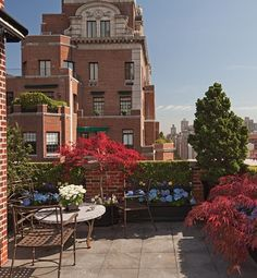 This colorful terrace off an apartment in a 1929 building on Park Avenue is landscaped with hydrangeas, pansies, boxwood, and red maples. The pale stone paving contrasts with the bright flowers and black planters. The master bedroom includes a second smaller terrace, which displays a Jenny Holzer sculpture.