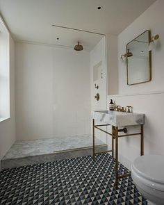 Modern bathroom features a brass washstand with marble sink fitted with a brass faucet under a ...
