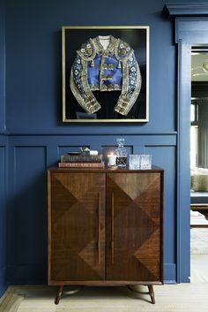 In the living room, a striking matador jacket is hung above a midcentury-inspired Mitchell Gold + Bob Williams bar | archdigest.com