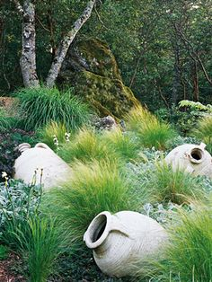Your favorite ornamental grasses can be the perfect complement to sculpture. Here, feathergrass creates an intriguing foil to broken pottery sculptures and lamb's ears. The effect is a contemporary design that will look great all year long.