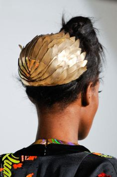 a golden, almost grecian, feathered hat worn over a hair bun. so cool and modern with a nostalgic vintage twist