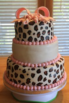 Cheetah print baby shower cake. Painted cheetah with black and brown & copper (mixed) gel colors by Americolor (dries very fast). Painted freehand. Bow made from MF & gumpaste. Cake covered with BC icing and MF. Pink border made with MF.