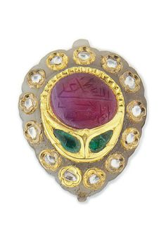 AN INSCRIBED GEMSET JADE PENDANT  INDIA, 19TH CENTURY  Of almond shape with cusped borders carved as a leaf on the underside, the front with a large ruby inscribed with the names of God, Muhammad, 'Ali, (F)atima, Hassan and Husayn, the diamonds arranged to form a flower with two petals surrounded by quatrefoils inset with diamonds, suspension loop at top