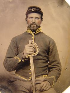 Unidentified soldier in Union cavalry uniform holding cavalry saber. From: Soldiers of the Civil War.