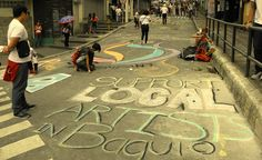 Local artists in Baguio City make a statement by writing on the pavement of Session Road using colored chalk sticks.