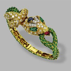 GREEN ENAMEL AND DIAMOND SNAKE BANGLE-BRACELET, DAVID WEBB The articulated snake formed of scale-like links applied with translucent green enamel, the head decorated with numerous round diamonds, 1 cushion-shaped sapphire, 2 pear-shaped emerald eyes and a pear-shaped ruby tongue, mounted in 18 karat gold and platinum, signed Webb.