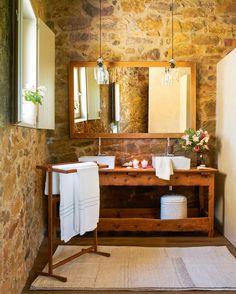 Baño rústico con paredes de piedra, bajolavabo de madera antiguo, toallero de pie, espejo y lámparas colgantes (00391515)