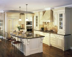 This kitchen features beautiful detailed cabinetry, with a matching style around the base of the island. Do you like the granite countertops?