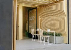Los Angeles firm A-Industrial has clad the walls and ceiling of a juice bar in plywood slats, creating a sculptural geometric interior