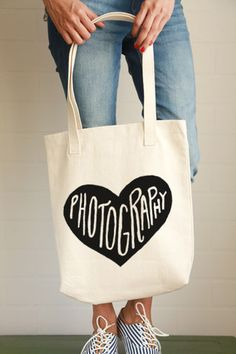 "Whether you love photography or photography loves you, this adorable tote bag is for you! - 12.0 oz., 100% cotton canvas - 22"" handles - Reinforced bottom - The design is printed using water based ink"