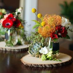 love these center pieces. pincushion protea and billy balls are 2 of my favorites... love the wood too.