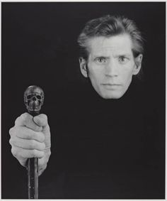 Robert Mapplethorpe   This photograph was taken a few months before he died from an AIDS-related illness in 1989. In it he faces straight ahead, as if he were looking death in the face. The skull-headed cane that he holds reinforces this reading. Mapplethorpe is wearing black, so that his head floats free, disembodied, as if he were already half-way to death. Mapplethorpe even photographs his head slightly out of focus to suggest his gradual fading away.