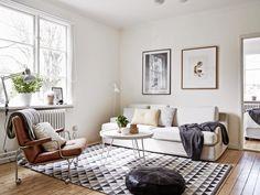 Canap blanc, coussins, plaid, table ronde, lampe allu, plantes, tapis graphique
