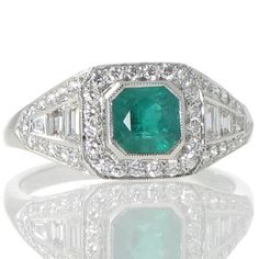 A platinum dress ring set with a central square 0.68ct emerald set in a plaque of 0.75cts of diamonds. www.rutherford.com.au