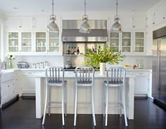 White kitchen with glass upper cabinets + stools