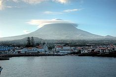 The vista off the coast of Madalena parish, showing the profile of the stratovolcano Pico and settlement of the municipal seat