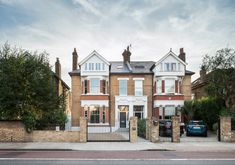 Grand Edwardian family house restoration Restoration of a semi detached period house in London. Beautiful yellow and red brick facade building with front driveway and electric sliding gate