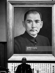 Nationalist Chinese president Chiang Kai-Shek appears dwarfed by a mammoth picture of the father of Chinese Democracy, Dr. Sun Yat-Sen, as he speaks before members of the National Assembly and government officials at a meeting marking the 20th anniversary of the promulgation of the Chinese Constitution. Chiang, who reached 80 recently and still appears to be in his usual fine health, was attired in a plain Sun Yat-Sen suit.