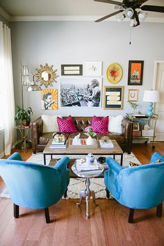 Colorful and eclectic living room with blue armchairs, pink pillows, and gallery wall