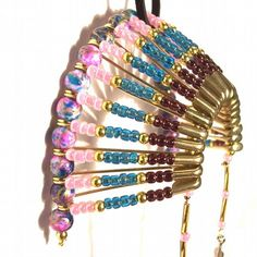 Was $20.00 now $16.00. This Beautiful headdress is made of brass Safetypins and shades of purple, blue, pink glass beads. Hang it from your rearview mirror or hang it in your window and admire the bea