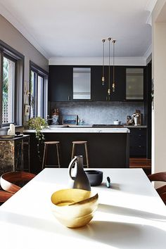 Black modern kitchen with white marble counters.