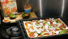 Pizza met parmaham, avocado, mozzarella, crème fraîche en bascilicum