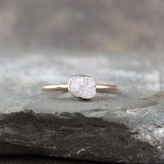 A unique raw, uncut, rough genuine diamond is the highlight on this 14K pink gold solitaire ring. The natural rough diamond is unique - exactly the