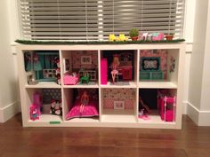 Sage's Dreamhouse. Created out of an Ikea Expedit shelf. Walls are chalkboard paint, wrapping paper or scrapbook paper. Furniture is a mix of handmade, barbie and ikea. Closet is made out of a spray painted crate with a bike spoke rod. Bed is made out of a storage box with handmade bedding.  Rooftop patio is a custom faux grass rug. Sage Leaf studio custom creations 2013.