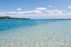 The crystal clear water of Torch Lake fades to aqua blue from the sandbar near its southern outlet.