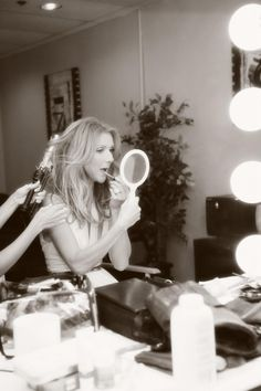 Celine Dion doing her lips and looking in the mirror